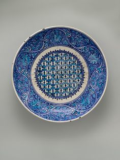 Dish | Iznik, Turkey, mid-16th century | Stonepaste; painted in turquoise and two hues of blue under transparent glaze | This saucer‑shaped dish displays a palette of rich blue and bright turquoise characteristic of early Iznik ceramics | The floral scrolls on the cavetto are inspired by fifteenth-century Chinese celadon ware | The Metropolitan Museum of Art, New York