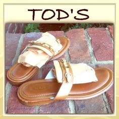 "Tod's thong sandals Understated elegance, even in your flip flops. Tobacco leather sandals, complimented by tan leather and gold colored hardware (two little buckles and a center ""ring""). Another great thing about these thong sandals is that they aren't completely flat. They boast a nice little one inch wooden heel. The footbed is cushioned well too. A very well made shoe. Preloved, there really are just slight signs of wear to the wood heel and sole, other than the bottom (which is simply…"