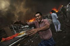 A man shouts for water as a shanty town is engulfed in flames in New Delhi, India.