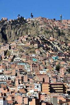 La Paz, Bolivia. As it grew, the city of La Paz climbed the hills, resulting in varying elevations from 10,500 to 13,500 ft. Overlooking the city is towering triple-peaked Illimani, which is always snow-covered and can be seen from several spots of the city, including from the neighboring city of El Alto.