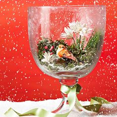 Open Air Snow Globe ~ Create a mini winter wonderland in your own home with this open-air snow globe. Crafts store staples easily turn a clear glass hurricane (this one is about 15 inches tall) into your own personalized Christmas landscape. Arrange moss, faux berries, and paper flowers inside. Add a faux bird, then spray with faux snow. For extra shimmer, add a touch of frosted-glass spray on the outside.