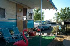 retro camper with flamingo, cooler, yard chairs and a classic car