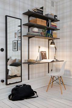 Un coin bureau noir dans une entrée avec un déco portée par un papier-peint à carreaux vintage