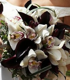 White orchids and black cala lilies bouquet. <3 Simply stunning. I love the way they both have a deep maroon tint to match each other and the yellow in the orchids is a beautiful pop of color. Very cohesive and elegant for a black and white wedding bouquet.  Runway Fashions About Weddings: What Kinds of Bridal Bouquets Will You Choose For Winter Weddings