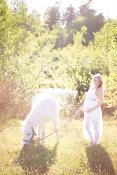 Maternity inspiration. White gown, delicate flower crown, White pony by the pond.