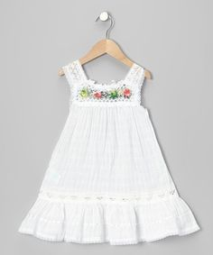 Handmade in Ecuador, this breezy dress is the perfect sunny-day staple or lively layer for grayer days. Hand-stitched, one-of-a-kind flowers complement the darling crocheted bodice. This product cannot be shipped to New York or Wisconsin