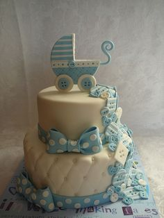 A buttons cascade and baby carriage for a baby boy baptism. The baby carriage is hand made with fondant. This is a vanilla cake with buttercream icing covered with fondant. All decorations are fondant.
