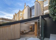 Curvy timber extension by Scott Architects with a sloping grass roof