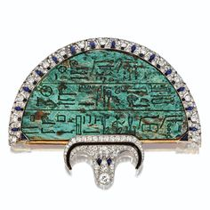 Egyptian-Revival Jeweled Fan Brooch, Cartier, London, 1923 Composed of an Egyptian glazed steatite plaque of semicircular shape, circa 600 B.C., inscribed with hieroglyphs, the border of papyrus and lotus motifs decorated with pear-shaped cabochon sapphires and square segments of onyx and enamel within a ground of pavé-set old European-cut and single-cut diamonds, the base centering a stylized lotus blossom similarly set with old European-cut, single-cut and rose-cut diamonds