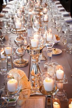 Shiny silver candlesticks topped with votive candles as wedding reception centerpieces.