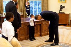 """President Barack Obama bends over so the son of a White House staff member can pat his head during a family visit to the Oval Office May 8, 2009. The youngster wanted to see if the President's haircut felt like his own. (Official White House Photo by Pete Souza)"""