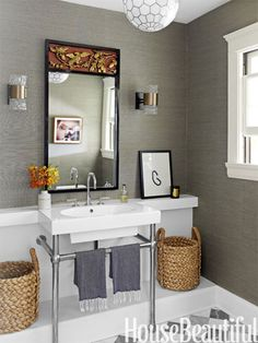 Gray grass cloth in the powder room sets off a vintage mirror and sconces, and the harlequin pattern of the floor tiles lends geometric punch. Designer: Christos Prevezanos