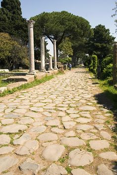 Roman Road_ Ostia Antica_Sheila Terry /This road runs through Ostia Antica, an ancient Roman seaport built at the mouth of the Tiber River near Rome,.The port was founded by the Roman king Ancus Marcius in about 620 BC and was used to import grain and other essentials. Roman roads generally contained four layers. The top layer was usually cemented flag stone, below which were various levels of sand, gravel and aggregate. These roads are still intact today and can be found from Scotland to…