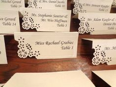 Paper cut escort cards: Hand made escort cards, using plain white cards then paper punching the corners using a cut-out tool by Martha Stewart crafts