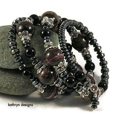 This funky bracelet features an earthy, unique mix of gorgeous stone beads in rich shades of black, grey, and eggplant. The mix of beads creates artsy look that will easily dress up any outfit. This statement bracelet is full of sparkle and rich color.