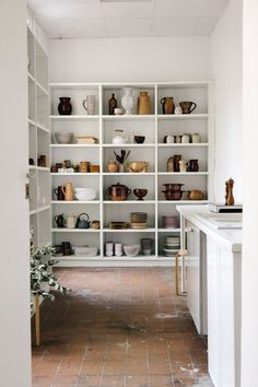 White bookshelves storing kitchen bowls and vessels great color coordinated kitchen storage