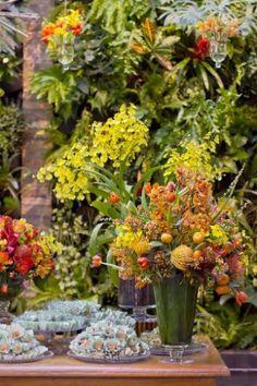 Nesse exuberante arranjo de primavera/verão, proteas, orquídeas Cymbidium e Dendrobium, sementes e mini mexericas enfeitam a mesa de doces, em um conjunto criado pela Flor e Forma