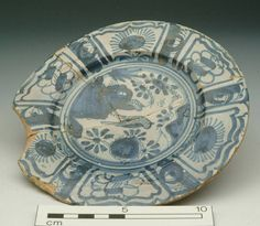 Accession number: 24368 Collection place: Pickleherring, Southwalk, London 1626-1630 Earthenware H 14 mm; DM 176 mm Post-Medieval Almost complete English tin-glazed ware plate, decorated in deep blue and blue-wash with a bird-on-rock pattern surrounded by six Ming-style panels round rim, on an off-white glaze, back buff. This is thought to be one of the earliest articles with bird-on-rock decoration and is remarkable for its flat profile. From brick-lined cess pit in trench VIII.