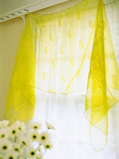 A faux-silk scarf (approximately 20x90 inches) adds sheer elegance to this window. Look for scarves at consignment shops or thrift stores. Stitch earring hooks (for pierced ears) to one edge to hang the scarf from a decorative nail in the crown molding or window frame. This type of treatment is best in a breakfast area, where the scarf wont be hit by splashing water or steam from cooking.