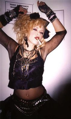 1980s Madonna style. Note the crucifix necklaces, crop top, fishnet top, lace fingerless gloves, studded belts, bow in the hair, and a stack of bangles and jelly braclets on the arms.