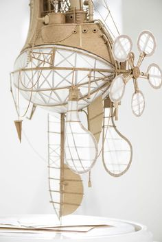 """Netherlands-based artist Jeroen van Kesteren has created these sculptural airships as part of a series titled """"Orphanage for Lost Adventures"""". Made primarily from cardboard, aluminum foil, adhesives, and an assortment of papers used for sails and propellers, the whimsical flying machines have a distinct steampunk feel. The pieces range in 40 to 50 centimeters tall …"""