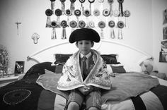 A young boy sits on his bed