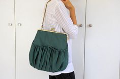 A green kisslock bag, with big pleated pockets on the outside and a strong kisslock closure. Made out of the finest Italian upholstery fabric in dark