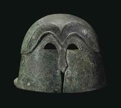 A GREEK BRONZE PSEUDO-CORINTHIAN HELMET - MAGNA GRAECIA, CLASSICAL PERIOD, CIRCA 5TH CENTURY B.C. - Formed of hammered sheet, of domed form, with a broad rear flange, the high-arching, M-shaped, raised eyebrows mirrored above & extending to the carinated ridge encircling the crown, the small false eye holes & nose-guard cut out & outlined with incised chevrons, the false cheek-pieces incised with confronting boars, with zigzag along the rim, 9 ¾ in.  long