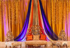 a vibrant gold backdrop with shimmering crystal accents from the drapes, accented with a pop colbalt blue and orange fabric gathered in the middle and our vintage furniture set, a hint of royalty but with the flair of Asian elegance