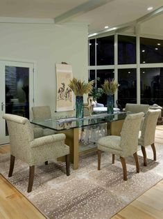 This contemporary dining room features a glass table with a family-crest base. Slipper chairs and arm chairs in the same upholstery create a unified look. A Chinese scroll adds refinement.