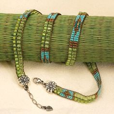 Santa Fe artist, Adonnah Langer of Chili Rose Beadz, introduces a beautiful Southwest inspired wrap bracelet of blue and copper seed beads, gorgeously at play in a sea of vivid green. Twine this unique bracelet up to four times around your wrist and enjoy a pattern that alternates between simply stunning and wonderfully complex. The clasp features Chili Rose's signature sterling silver terminals, showcasing a beautifully carved flower design exclusive to Chili Rose.