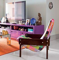 Tudo vibra: do móvel de TV roxo ao tapete laranja. O tecido pixelado também é colorido e deu nova vida à poltrona Vronka, de Sergio Rodrigues. Projeto da arquiteta Andrea Murao