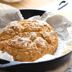 Baked Irish Soda Bread on parchment paper in a cast iron skillet.