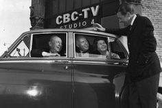 Panel member Gordon Sinclair, Pierre Berton, Betty Kennedy and host Fred David pose in front of CBC-TV Studio 4 in Toronto to promote Front Page Challenge.