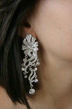 David Tutera Marissa Dangle Earring With a dramatic profile these chandelier earrings host an array of crystals in solid white pave tiered, intricately textured design.  #weddings  #bridal jewelry  See them here  http://www.victoriarosebridals.com/shop/marissa-dangle-earring/