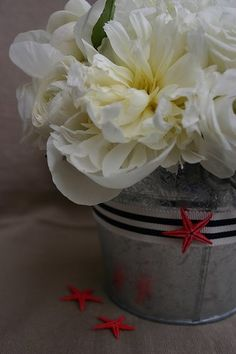 Love this centerpiece - minus the starfish.  Lush flowers + galvanized pail + ribbon is super class though, IMO.