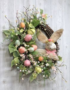 Easter Bunny Wreath, Easter Decorations, Easter Wreath, Spring Wreath for Front Door, Easter Decor, Easter Eggs, Easter Bunny, Free Shipping Easter Bunny Wreath......a cute (11 tall) natural sisal (straw) Easter bunny with bendable fur ears and wearing a crown of spring flowers, is the center of this unique wreath! Designed by The Wreath Shed, this one of a kind beautifully designed Easter bunny wreath is made on a grapevine wreath base with natural grapevine added. Included in this wreath…