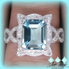 Aquamarine Engagement Ring. This beautiful ring features an 8mm x 10mm emerald cut aquamarine set in a 14K white gold picture frame halo setting. Available with