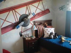 Classic aviation themed bedroom- wall mural plus a ceiling fan blade for the airplane.  Genius!