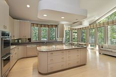 Large white kitchen with smooth cabinets and smooth, rounded island.  Kitchen area surrounded by windows creating a light and airy kitchen space.