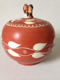 Really sweet, small hand-made terracotta pot wit lid.  This exquisite little pot is just the sweetest thing.  Made from red terracotta; glazed on the outside.  White leaf pattern encircles the main body of the pot with a matching design on the lid.  Hand painted in a very ethnic looking style. The knob on the lid is fashioned into two figures of a couple embracing..... could they be a native American bride and her groom?  This is a very unusual looking piece that would make a really lovely…