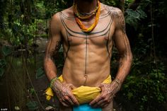 Australian filmmaker and tattooist Rob Henry, sporting body tattoo designs of Mentawai tribe origin, poses for a photograph in the jungle