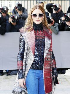 Olivia Palermo wears a sequin turtleneck, vest, jeans, flap bag, and round sunglasses