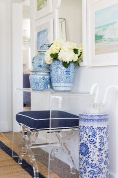 Gorgeous blue and white styling. Navy stool under ghost console table lucite, ginger jars, coastal decor
