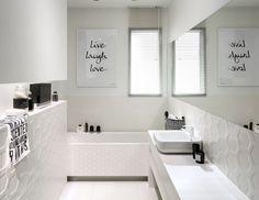 Badezimmer mit weißen Fliesen und schwarzen Akzenten an der Wand