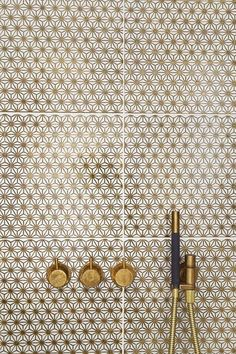 gold + white pattern tile w/brass fixtures