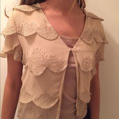 Stunning scalloped short sleeved blouse Beautiful beige blouse by ThistlePearl with lots of detail. Back has layered scalloping with glitter and sequined detail. Front has a low V to a hook closure and opening the rest of the way down. Only worn a few times. Urban Outfitters Tops Blouses