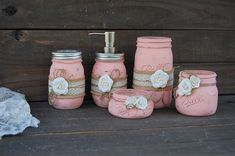 """Shabby chic mason jar bathroom jar set. Hand painted in soft peach, lightly distressed, wrapped with burlap, lace, tied with jute and ivory roses, finished with a protective coating. 5 piece set. Soap dispenser, toothbrush holder, make up brush holder, cotton swab jar, cotton ball jar, or many other uses! Do not immerse in water, clean with a damp cloth. The jars range in height from 6.5"""" to 2"""" tall and 3.5"""" to 3"""" in diameter. This set can be painted any color you like, or with any…"""