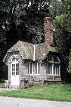 Teeny tiny summer house with a half-hip or clipped gable roof and a very large chimney!