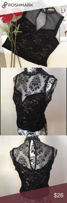 Illusion net & lace top Demure black embroidered lace with sheer illusion net upper bodice. Lace trim at neckline & armholes. Two buttons fasten at back of neck, slit opening upper back. Lower bodice is lined. Material is nylon , chenille, spandex blend. Very pretty! Olive Tree Tops
